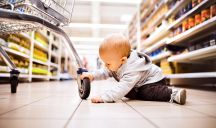 Bimbo gioca sdraiato sul pavimento del supermercato