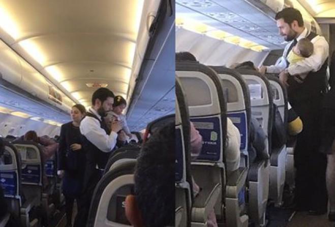 assistente di volo prende in braccio due bambini
