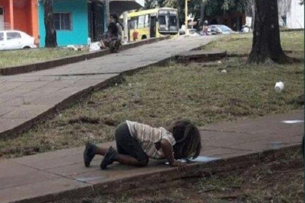 Bimba indigena beve da una pozzanghera