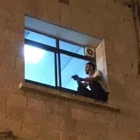 Figlio seduto alla finestra della camera di ospedale in cui la mamma sta morendo