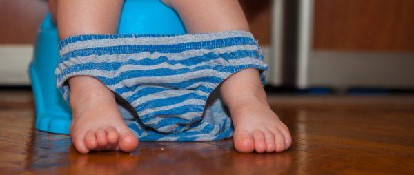 bambino seduto sul vasino trattiene la cacca