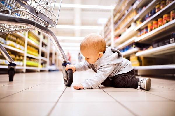 Bimbo gioca sdraiato sul pavimento del supermercato video